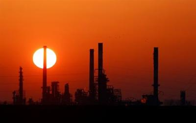 FILE PHOTO: The sun sets behind the chimneys of the Total Grandpuits oil refinery, southeast of Paris, France, March 1, 2021. REUTERS/Christian Hartmann