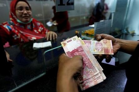 FILE PHOTO: A customer holds Indonesian rupiah bank notes at a money changer in Jakarta, Indonesia August 13, 2018. REUTERS/Willy Kurniawan/File Photo