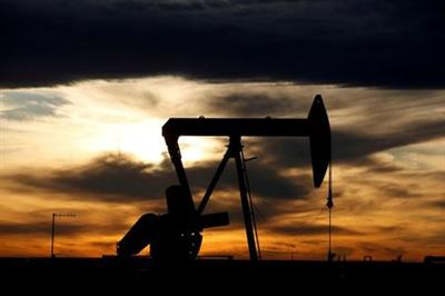 FILE PHOTO: The sun sets behind a crude oil pump jack on a drill pad in the Permian Basin in Loving County, Texas, U.S. November 24, 2019. REUTERS/Angus Mordant/File Photo
