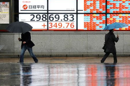 Men holding umbrellas walk in front of an electric board showing Nikkei index at a brokerage in Tokyo, Japan February 15, 2021. REUTERS/Kim Kyung-Hoon