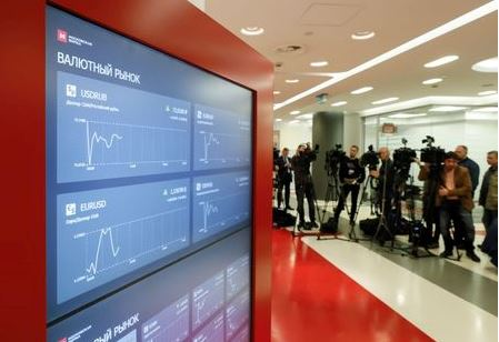 Journalists gather near screens showing currency exchange rates, share price index and other information in the office of the Moscow Exchange in Moscow, Russia March 10, 2020. REUTERS/Shamil Zhumatov