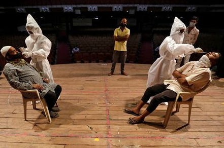 Healthcare workers wearing personal protective equipment (PPE) collect swab samples from men during a rapid antigen testing campaign for the coronavirus disease (COVID-19), at an auditorium turned into a testing centre in Ahmedabad, India, March 23, 2021. REUTERS/Amit Dave