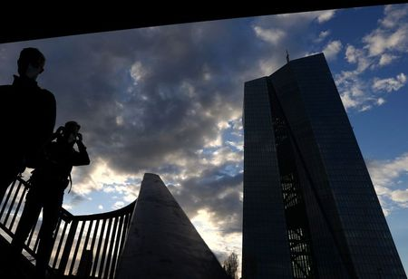 People are silhouetted in front of the head quarter of the European Central Bank (ECB,R) during sunset as the spread of the coronavirus disease (COVID-19) continues in Frankfurt, Germany, March 27, 2021. REUTERS/Kai Pfaffenbach