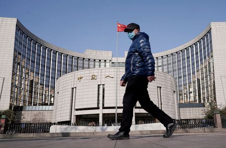 A man wearing a mask walks past the headquarters of the People's Bank of China, the central bank, in Beijing, China, as the country is hit by an outbreak of the new coronavirus, February 3, 2020. REUTERS/Jason Lee