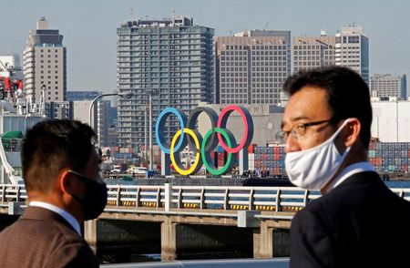 FILE PHOTO: Men wearing face masks watch as giant Olympic rings, which were temporarily taken down in August for maintenance amid the coronavirus disease (COVID-19) outbreak, are transported for reinstallation at the waterfront area at Odaiba Marine Park in Tokyo, Japan December 1, 2020. REUTERS/Kim Kyung-Hoon/File Photo