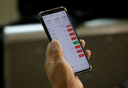 An investor checks share prices on his mobile phone at a brokerage office in Beijing, China January 2, 2020. REUTERS/Jason Lee