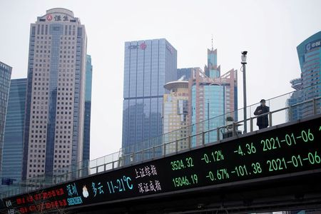 FILE PHOTO: A man stands on an overpass with an electronic board showing Shanghai and Shenzhen stock indexes, at the Lujiazui financial district in Shanghai, China January 6, 2021. REUTERS/Aly Song