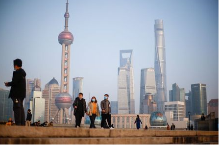 People walk at the Bund, in front of Lujiazui financial district of Pudong, on the day of the opening session of the Chinese People's Political Consultative Conference (CPPCC), in Shanghai, China March 4, 2021. REUTERS/Aly Song