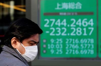 A man wearing a surgical mask stands in front of a screen showing Shanghai Composite index outside a brokerage in Tokyo, Japan February 3, 2020. REUTERS/Kim Kyung-Hoon