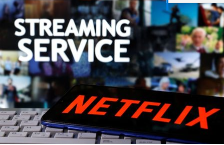 "A smartphone with the Netflix logo is seen on a keyboard in front of displayed ""Streaming service"" words in this illustration taken March 24, 2020. REUTERS/Dado Ruvic"