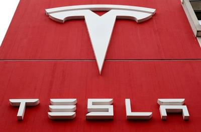 FILE PHOTO: The logo of car manufacturer Tesla is seen at a branch office in Bern, Switzerland October 28, 2020. REUTERS/Arnd Wiegmann/File Photo