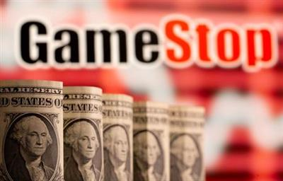FILE PHOTO: U.S. one dollar banknotes are seen in front of displayed GameStop logo in this illustration taken February 8, 2021. REUTERS/Dado Ruvic/Illustration/File Photo
