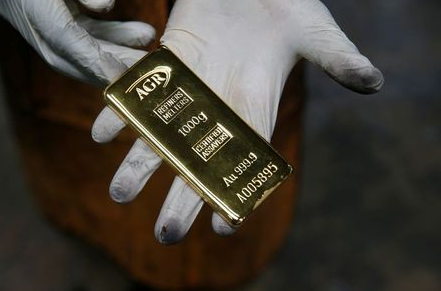 FILE PHOTO: An employee holds a 1kg gold bar at AGR (African Gold Refinery) in Entebbe, Uganda, October 4, 2018. REUTERS/Baz Ratner/File photo