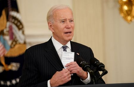 U.S. President Joe Biden holds a card with the number of people who have died of the Coronavirus disease as he delivers remarks on the state of the coronavirus disease (COVID-19) vaccinations from the State Dining Room at the White House in Washington, D.C., U.S., April 6, 2021. REUTERS/Kevin Lamarque