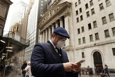 FILE PHOTO: A man walks past the New York Stock Exchange on the corner of Wall and Broad streets in New York City, New York, U.S., March 13, 2020. REUTERS/Lucas Jackson/File Photo