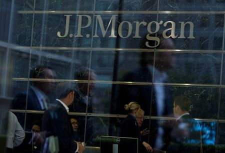 FILE PHOTO: Workers are reflected in the windows of the Canary Wharf offices of JP Morgan in London September 19, 2013. REUTERS/Neil Hall/File Photo