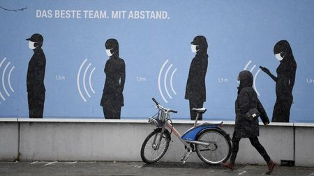 """FILE PHOTO: A woman walks next to a poster reading """"The best team. With distance."""" in front of a BMW factory as the spread of the coronavirus disease (COVID-19) continues in Munich, Germany, December 9, 2020. REUTERS/Andreas Gebert"""