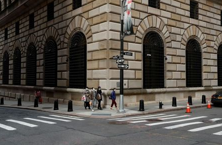 FILE PHOTO: People walk wearing masks outside The Federal Reserve Bank of New York in New York City, U.S., March 18, 2020. REUTERS/Lucas Jackson/File Photo/File Photo