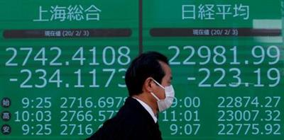 A man wearing a surgical mask walks past a screen showing Shanghai Composite index and Nikkei index outside a brokerage in Tokyo, Japan February 3, 2020. REUTERS/Kim Kyung-Hoon