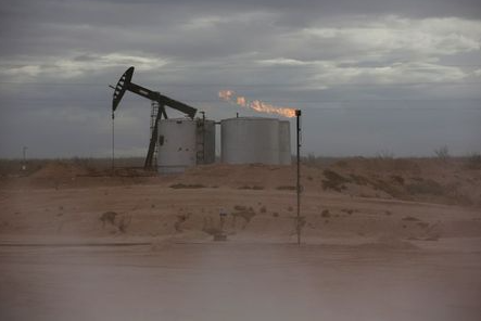 FILE PHOTO: Dust blows around a crude oil pump jack and flare burning excess gas at a drill pad in the Permian Basin in Loving County, Texas, U.S. November 25, 2019. REUTERS/Angus Mordant/File Photo
