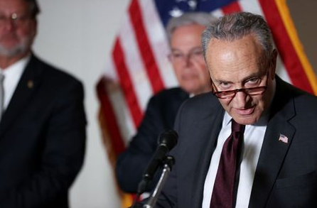 U.S. Senate Majority Leader Chuck Schumer (D-NY), with Senator Gary Peters (D-MI) and Senator Bob Menendez (D-NJ), speaks to reporters during the weekly news conference following the Democratic caucus policy luncheon on Capitol Hill in Washington, U.S. May 18, 2021. REUTERS/Jonathan Ernst