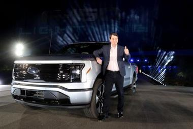 Ford CEO Jim Farley poses with the all-electric Ford F-150 Lightning pickup truck during the unveiling at the company's world headquarters in Dearborn, Michigan, U.S., May 19, 2021. REUTERS/Rebecca Cook