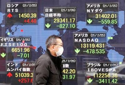FILE PHOTO: A man walks past a stock quotation board at a brokerage in Tokyo, Japan February 26, 2021. REUTERS/Kim Kyung-Hoon