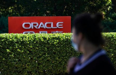 A pedestrian wearing face mask following the COVID-19 outbreak walks past a sign of Oracle in front of its office buildings in Beijing, China September 16, 2020. REUTERS/Tingshu Wang