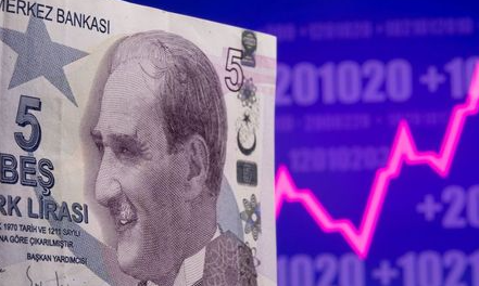 A Turkish lira banknote is seen in front of displayed stock graph in this illustration taken May 7, 2021. REUTERS/Dado Ruvic/Illustration