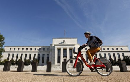 A cyclist passes the Federal Reserve headquarters in Washington September 16, 2015. The Federal Reserve, facing this week its biggest policy decision yet under Chair Janet Yellen, puts its credibility on the line regardless of whether it waits or raises interest rates for the first time in nearly a decade. REUTERS/Kevin Lamarque