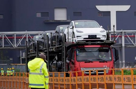 FILE PHOTO: A truck transports new Tesla cars at its factory in Shanghai, China, May 13, 2021. REUTERS/Aly Song/File Photo