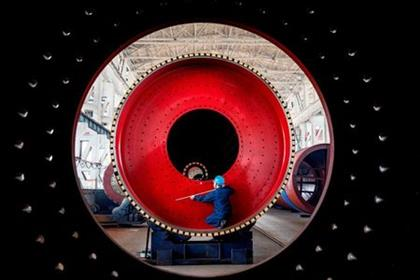An employee measures a newly manufactured ball mill machine at a factory in Nantong, Jiangsu province, China June 28, 2019. Picture taken through a ball mill machine June 28, 2019. REUTERS/Stringer ATTENTION EDITORS - THIS IMAGE WAS PROVIDED BY A THIRD PARTY. CHINA OUT. TPX IMAGES OF THE DAY