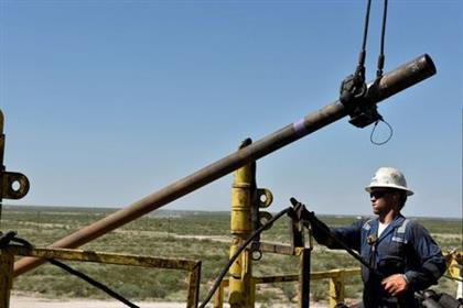 FILE PHOTO: A drilling crew member raises drill pipe onto the drilling rig floor on an oil rig in the Permian Basin near Wink, Texas U.S. August 22, 2018. Picture taken August 22, 2018. REUTERS/Nick Oxford/File Photo