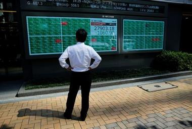 A man watches an electric board showing Nikkei index outside a brokerage at a business district in Tokyo, Japan, June 21, 2021. REUTERS/Kim Kyung-Hoon