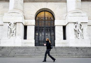 FILE PHOTO: A woman goes past the Italian Stock Exchange in Milan, as the country is hit by the coronavirus outbreak. Italy, February 25, 2020. REUTERS/Flavio Lo Scalzo/File Photo