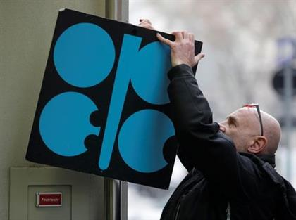 A man fixes a sign with OPEC's logo next to its headquarter's entrance before a meeting of OPEC oil ministers in Vienna, Austria, November 29, 2017. REUTERS/Heinz-Peter Bader
