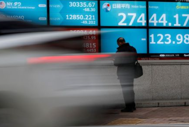 FILE PHOTO: A man stands in front of a screen displaying Nikkei share average and the world's stock indexes outside a brokerage, amid the coronavirus disease (COVID-19) outbreak, in Tokyo, Japan December 30, 2020. REUTERS/Issei Kato