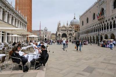 FILE PHOTO: People sit at outdoor tables at St. Mark's Square as Italy lifts quarantine restrictions for travellers arriving from European Union countries, Britain and Israel and begins offering COVID-free flights in a bid to revive the tourism industry, in Venice, Italy, May 16, 2021. REUTERS/Manuel Silvestri//File Photo