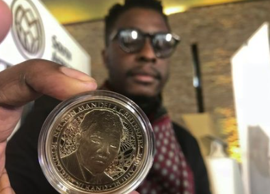 Zimbabwe-born Sindiso Nyoni holds a 1-ounce pure gold 5 rand coin that he designed, as the South African Reserve Bank (SARB) launched a set of limited edition bank notes and gold coins to mark the 100th anniversary of the birth of Nelson Mandela, in Pretoria, South Africa, July 13, 2018. REUTERS/Mfuneko Toyana