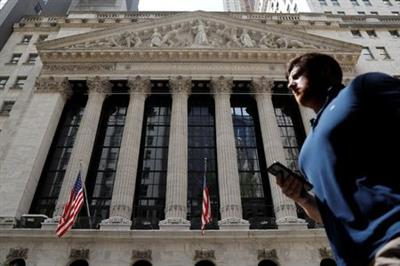 A person walks by the New York Stock Exchange (NYSE) in New York City, New York, U.S., July 19, 2021. REUTERS/Andrew Kelly