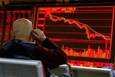 FILE PHOTO: An investor sits in front of a board showing stock information at a brokerage office in Beijing, China, December 7, 2018. REUTERS/Thomas Peter/File Photo