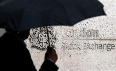 FILE PHOTO: A man shelters under an umbrella as he walks past the London Stock Exchange in London, Britain, August 24, 2015. REUTERS/Suzanne Plunkett/File Photo/File Photo