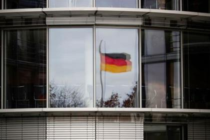 FILE PHOTO: A German flag is reflected in the window of the Paul Loebe building in Berlin, Germany, November 19, 2020. REUTERS/Hannibal Hanschke/File Photo