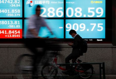 People ride bicycles past a screen displaying Nikkei share average outside a brokerage, amid the coronavirus disease (COVID-19) outbreak, in Tokyo, Japan May 11, 2021. REUTERS/Issei Kato