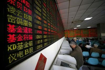 FILE PHOTO: Investors look at computer screens showing stock information at a brokerage house in Shanghai, China, April 21, 2016. REUTERS/Aly Song//File Photo