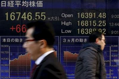 People walk past an electronic board displaying the Nikkei average outside a brokerage in Tokyo, Japan, March 2, 2016. REUTERS/Thomas Peter