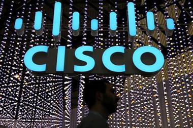 FILE PHOTO: A man passes under a Cisco sign at the Mobile World Congress in Barcelona, Spain, February 25, 2019. REUTERS/Sergio Perez/File Photo