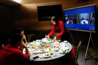 Liu Yuting and her family enjoy Chinese Lunar New Year dinner at a Haidilao hotpot restaurant with relatives in Jilin province connected via video link after they decided not to travel to their hometown following authorities advice after an outbreak of the coronavirus disease (COVID-19), in Beijing, China February 11, 2021. REUTERS/Carlos Garcia Rawlins