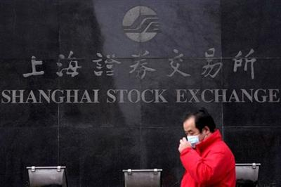 FILE PHOTO: A man walks past the Shanghai Stock Exchange building at the Pudong financial district in Shanghai, China, February 3, 2020. REUTERS/Aly Song