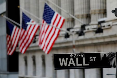 FILE PHOTO: American flags hang from the facade of the New York Stock Exchange (NYSE) building after the start of Thursday's trading session in Manhattan in New York City, New York, U.S., January 28, 2021. REUTERS/Mike Segar/File Photo